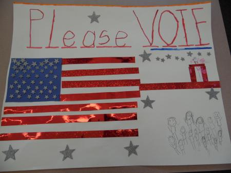 An-American-flag-made-from-shiny,-red-paper,-blue-paper,-and-silver-stars-is-on-the-left-side.-The-words-